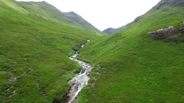 vídeos de stock e filmes b-roll de dramatic aerial / drone shot in glencoe along a river in the scottish highlands revealing mountains - vale