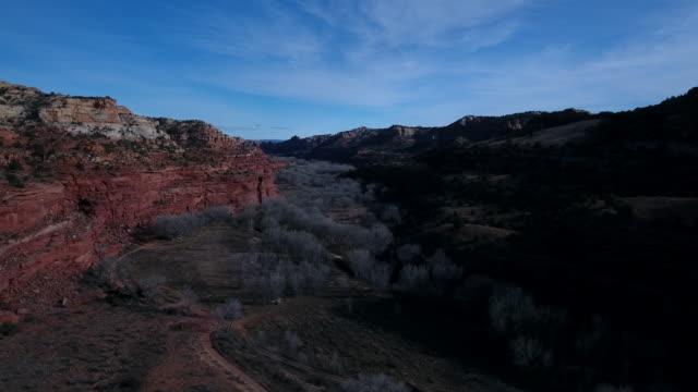 a dramatic aerial view of escalante looking over and the escalante river running through a grove of cottonwoods. escalante, utah, usa - escalante stock-videos und b-roll-filmmaterial