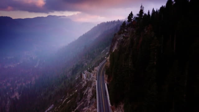 dramatic aerial view of highway in sierra nevada, ca - mountain range stock videos & royalty-free footage