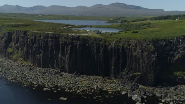 dramatic aerial view of the scottish countryside with a small lake and steep cliffs falling into the sea - hebrides stock videos & royalty-free footage