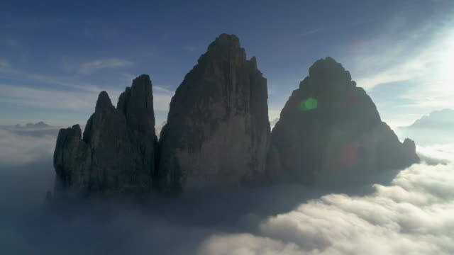 dramatic aerial views above the clouds showing tre cime di lavaredo, dolomites, italy - dramatic sky stock videos & royalty-free footage