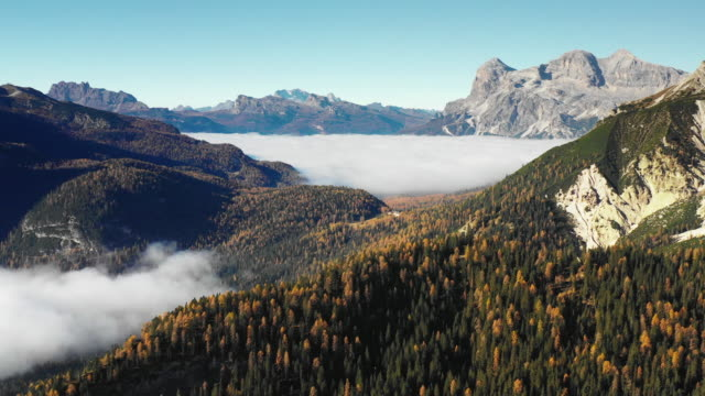 dramatic aerial views looking down a valley in the dolomites during autumn, italy - ロックストラータ点の映像素材/bロール