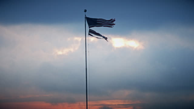 dramatic american flag blowing at sunset - bad condition stock videos & royalty-free footage