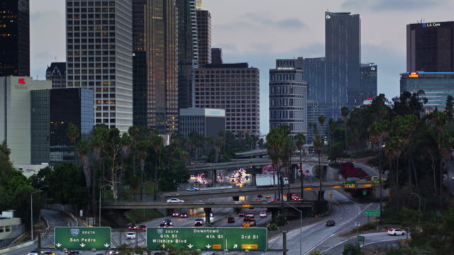 stockvideo's en b-roll-footage met dramatic ascending drone shot of i-110 traffic circling downtown los angeles - tilt up