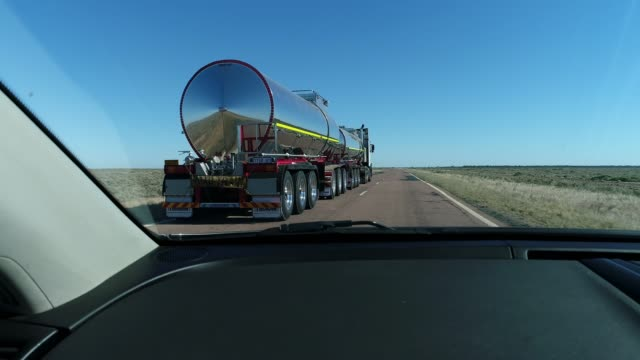dramatic car pov driving on desert highway overtaking shiny silver tanker in outback australia - overtaking stock videos and b-roll footage