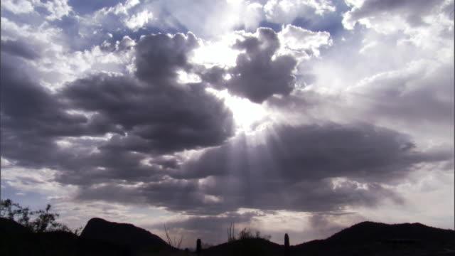 WS Dramatic clouds with sun beams shining through over desert landscape / Arizona, USA
