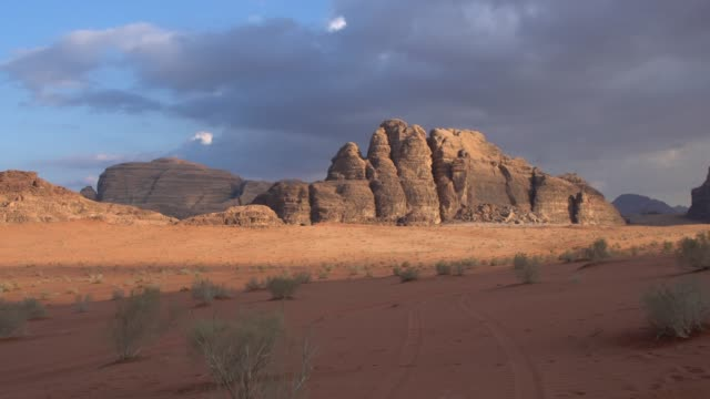 dramatic cloudy sky over the sandstone mountains in the wadi rum desert wilderness early in the morning, jordan - sandstone stock videos & royalty-free footage