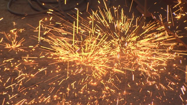 [flashing images] dramatic falling sparks disperse as they bounce off the concrete floor of a shipyard in glasgow, scotland. - sparks stock-videos und b-roll-filmmaterial