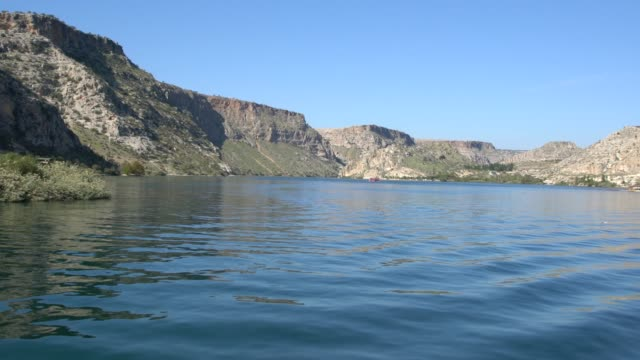 stockvideo's en b-roll-footage met dramatic landscapes with caves and big rock formations surround the dam on the euphrates at birecik, not far from the sunken village of halfeti, southeast turkey - dorp