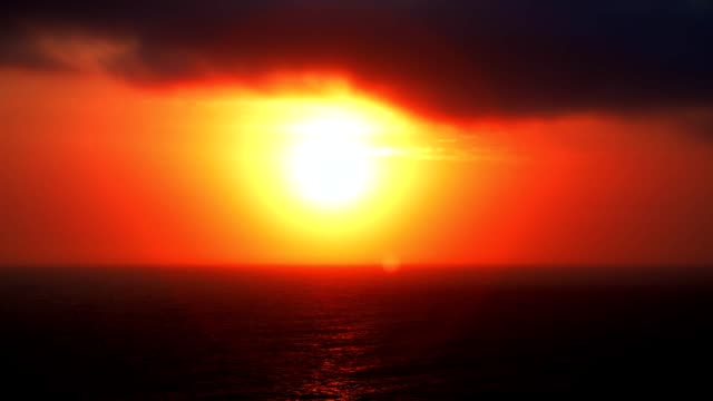 dramatic minimalist time lapse sunrise over the ocean set against a vivid red sky background in full hd - heatwave stock videos & royalty-free footage
