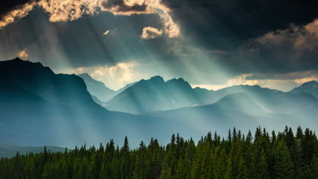 dramatic mountain landscape with sunbeams in canada - time lapse - area selvatica video stock e b–roll