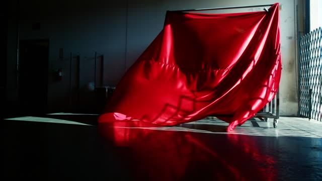 dramatic red silk fabric art installation blowing in warehouse - installationskunst stock-videos und b-roll-filmmaterial