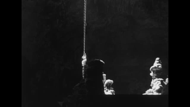 dramatic shot of a person climbing down a long, sunlit ladder hanging from the entrance of a cave into the massive cavern beneath / pan of... - baseball cap stock videos & royalty-free footage