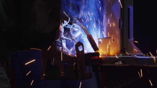 Dramatic shot of welders assembling steel parts in a US manufacturing factory.