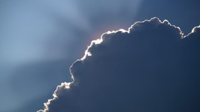 vídeos de stock e filmes b-roll de dramatic sun ray sunlight behind cloud - atrás