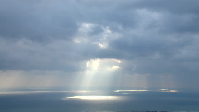 dramatic sunbeams shoot through storm clouds like a spotlight. - light beam stock videos & royalty-free footage