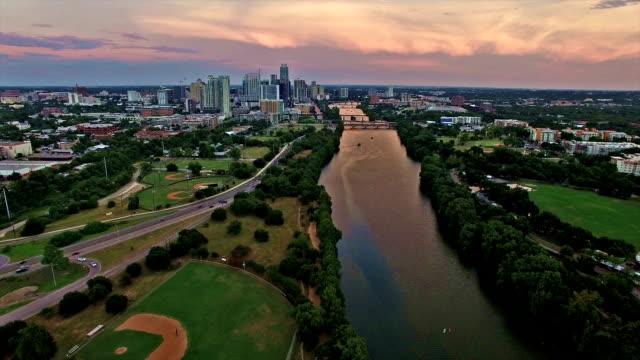Dramatische zonsondergang brengt kleuren naar het centrum van Texas Hill land de Skyline van de stad van Austin Texas Over Colorado rivier over honkbalveld