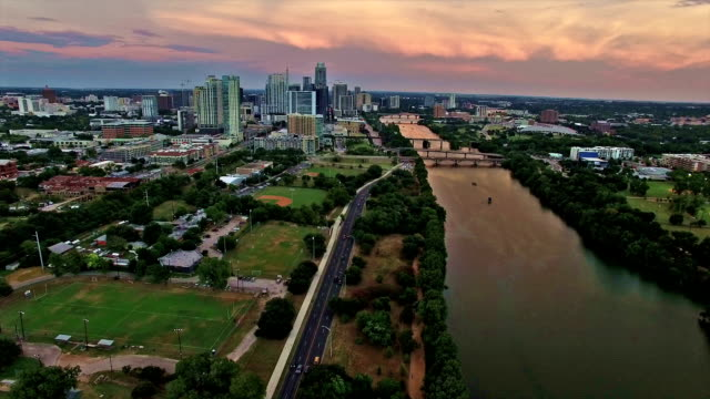 dramatic sunset brings colors to texas hill country downtown austin texas city skyline over colorado river over football field and outdoor parks - baseball diamond stock videos and b-roll footage