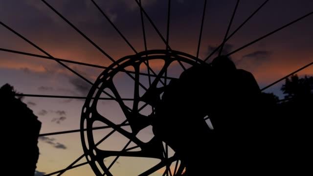 vidéos et rushes de nuages de coucher du soleil dramatiques time-lapse et roue de vélo de montagne - mountain bike