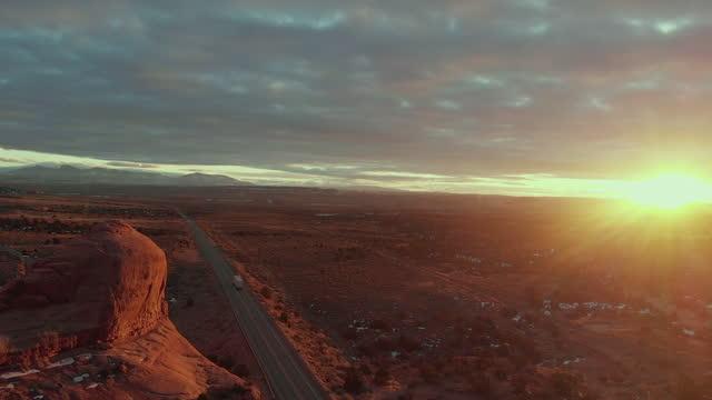 dramatischer sonnenuntergang des wilson arch, in der nähe von moab, utah, mit semi trucks, die die haupt-lkw-route befördern, die fracht liefert - moab utah stock-videos und b-roll-filmmaterial