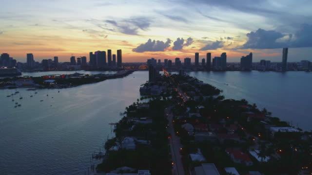 stockvideo's en b-roll-footage met dramatische zonsondergang over miami downtown en venetiaanse eilanden, florida, usa. de luchtdronevideo met de panning camera beweging. - venetian causeway bridge