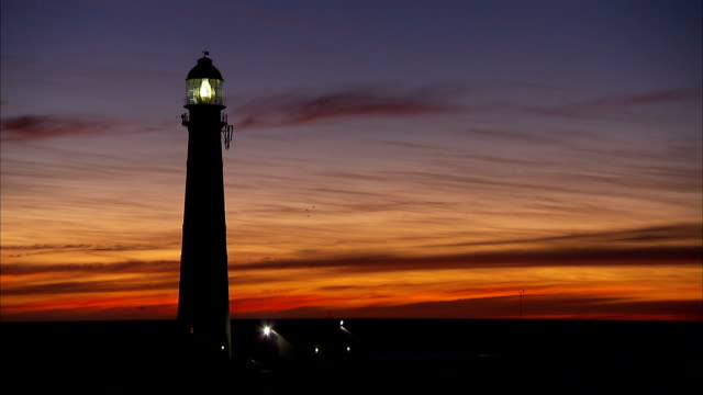 a dramatic sunset silhouettes a shining lighthouse. - dusk stock videos & royalty-free footage