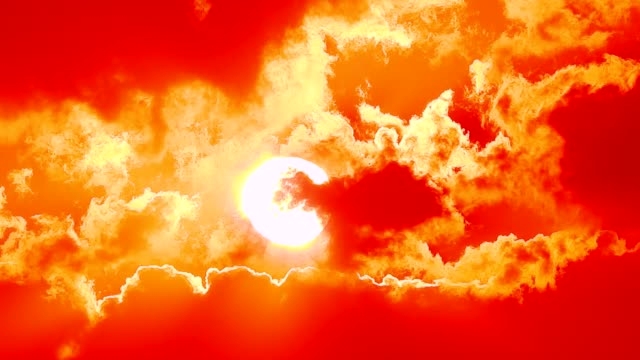 dramatic timelapse close up of setting sun warping through thick fiery clouds set against a vivid orange and red sky in full hd - bright stock videos & royalty-free footage