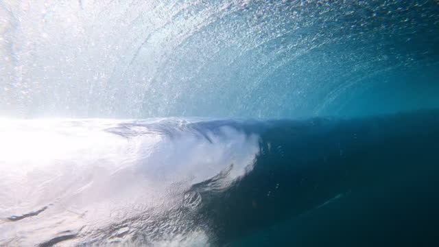dramatic underwater close-up of a large ocean wave rolling and breaking, with dark blue water, illuminated bubbles and reflected sunlight - oahu, hawaii - reinheit stock-videos und b-roll-filmmaterial