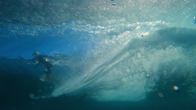 dramatic underwater of a large ocean wave rolling and breaking, with dark blue water, illuminated bubbles and a surfer flying across the surface above - oahu, hawaii - oahu stock videos & royalty-free footage