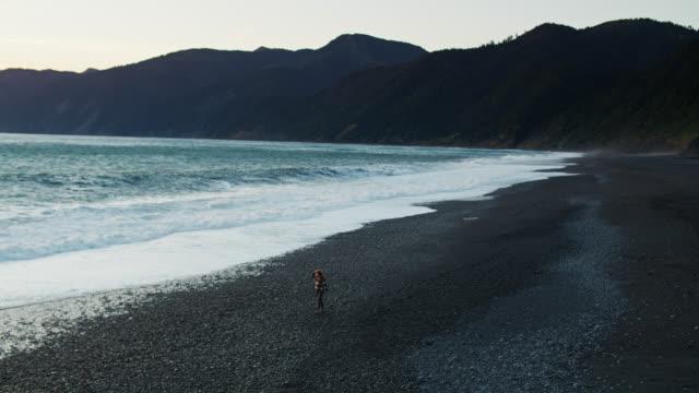 dramatic waves crashing towards woman walking on beach at sunset - aerial - black sand stock videos & royalty-free footage