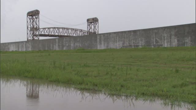 a drawbridge lowers near a flood wall and water-filled ditch. - drawbridge stock videos and b-roll footage