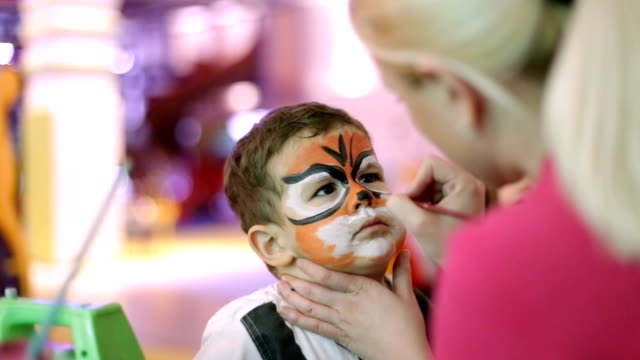 drawing a tiger on a child's face - toddler stock videos & royalty-free footage