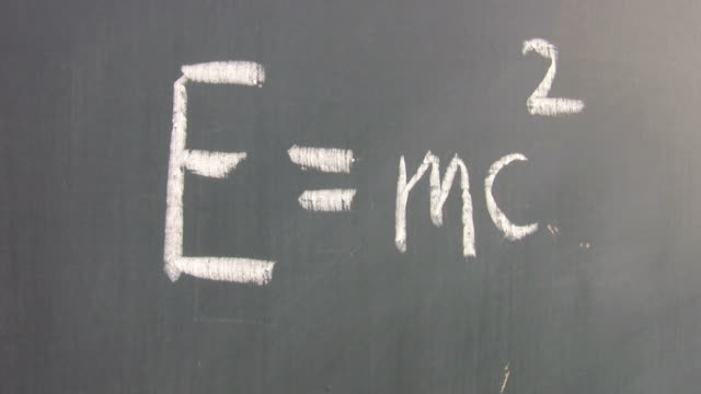 drawing the equation e = mc2 on a blackboard. - e=mc2 stock-videos und b-roll-filmmaterial