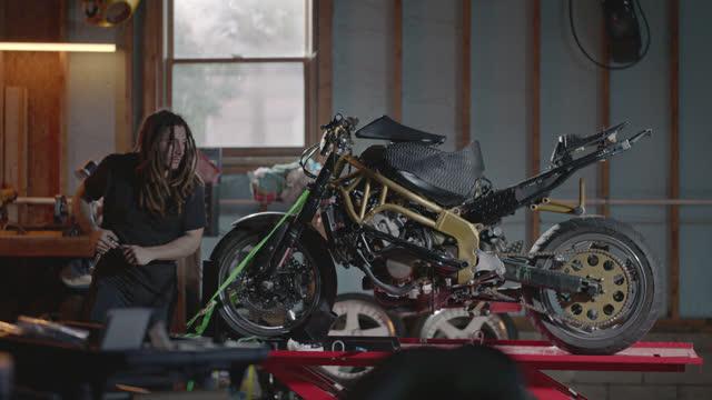dreadlocked man works on stunt motorcycle on hydraulic lift in garage repair shop. - maßgefertigt stock-videos und b-roll-filmmaterial