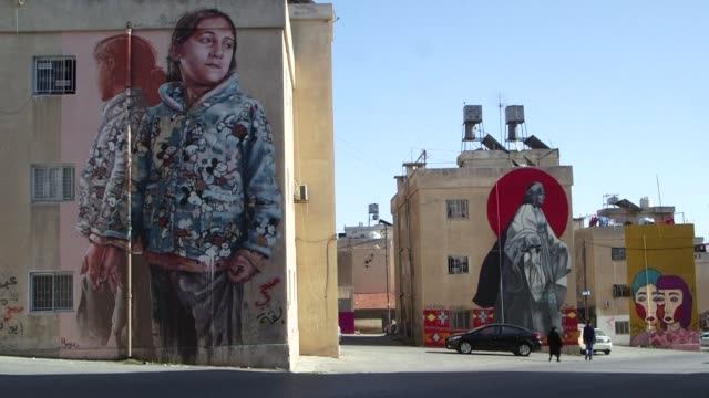 Dreadlocked university student Suhaib Attar clutches a can of spray paint as he sets to work on the latest gloomy corner of Jordan's capital that he...