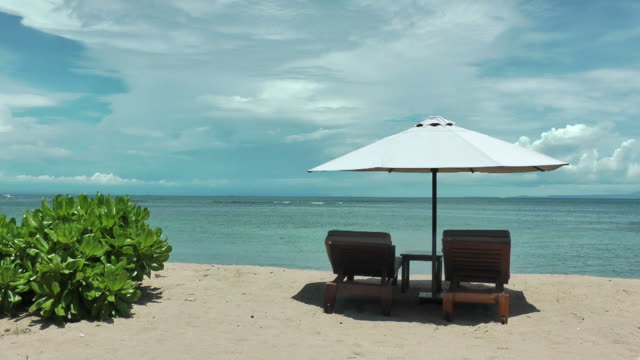 dream vacation; blue sky,  ochre sand, white beach umbrella - deckchair stock videos & royalty-free footage