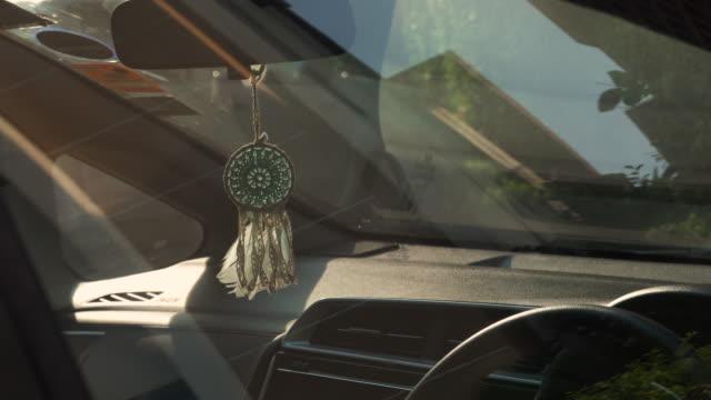 dreamcatcher hanging on inside car. - glowing doorway stock videos & royalty-free footage