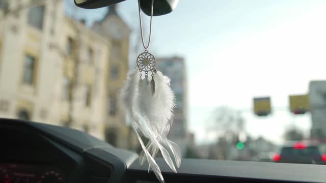 vidéos et rushes de dreamcatcher suspendu sur le rétroviseur dans la voiture - décoration de fête