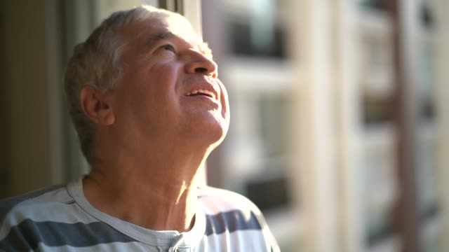 Dreamer senior man looking through window