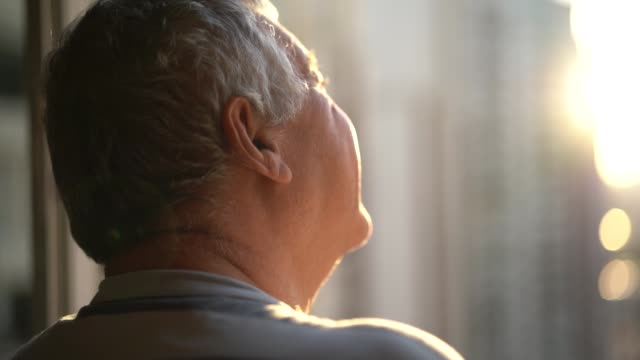 dreamer senior man looking through window - mature men stock videos & royalty-free footage