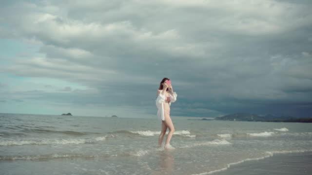 dreamlike walk with footprint on beach - beautiful woman stock videos & royalty-free footage