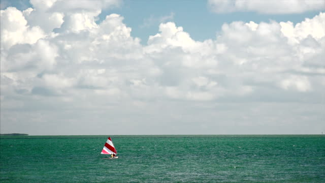dreamy sailboat with red and white striped sail in the tropical ocean of the florida keys - 鎖定觀看位置 個影片檔及 b 捲影像
