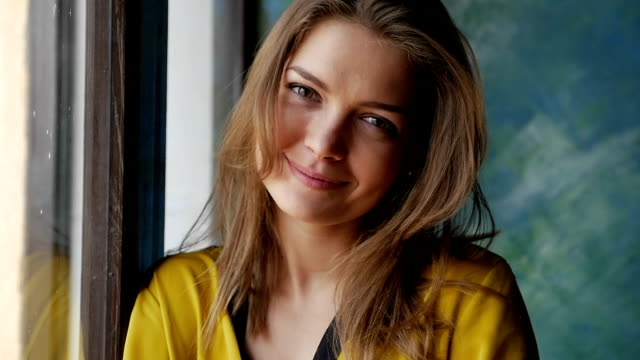 dreamy woman looking attentively at the camera while standing next to the window - blouse stock videos & royalty-free footage