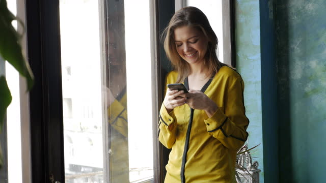 Verträumte Mädchen Blick durch das Fenster beim Telefonieren