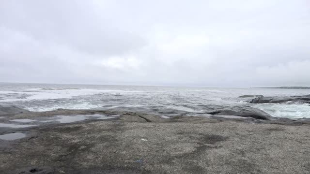 dreary sky above rough ocean scene beyond rocky shore - maine stock videos & royalty-free footage
