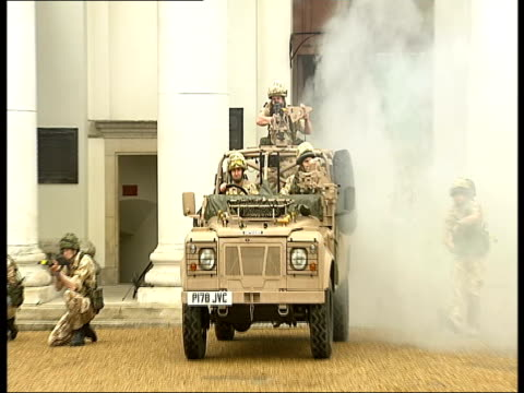 Dress rehearsals for Chelsea Pageant Armoured jeep enters quadrangle through doorway / Household Cavalry soldiers carry out mock battle with machine...