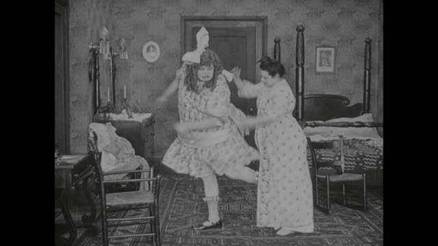 1917 dressed as girl, man (fatty arbuckle) kicks out at headmistress as she spanks him - spanking stock videos and b-roll footage