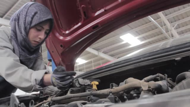 dressed in a baggy jumpsuit and a grey paisley veil 24 year old dalia al moqadam is an understated pioneer in yemen a rare female mechanic in a... - jumpsuit stock videos and b-roll footage