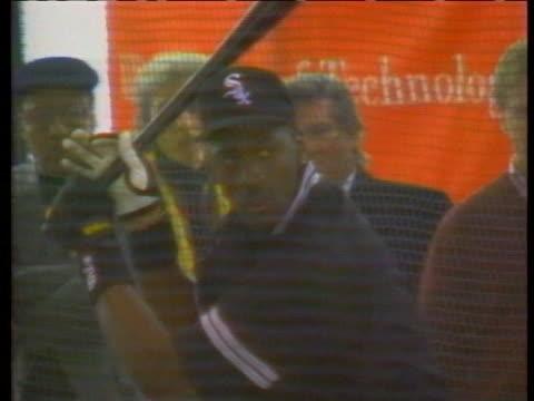 dressed in a chicago white sox uniform, michael jordan takes swings at baseballs in a batting cage. - gabbia di battuta video stock e b–roll