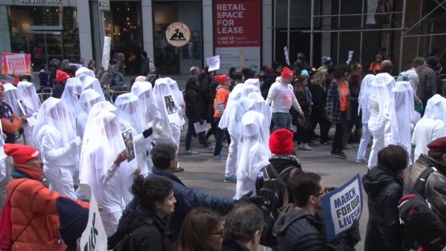 dressed in white veils and clothing protestors from the group gays against guns march down 7th avenue in silent protest / thousands of people many of... - march for our lives video stock e b–roll